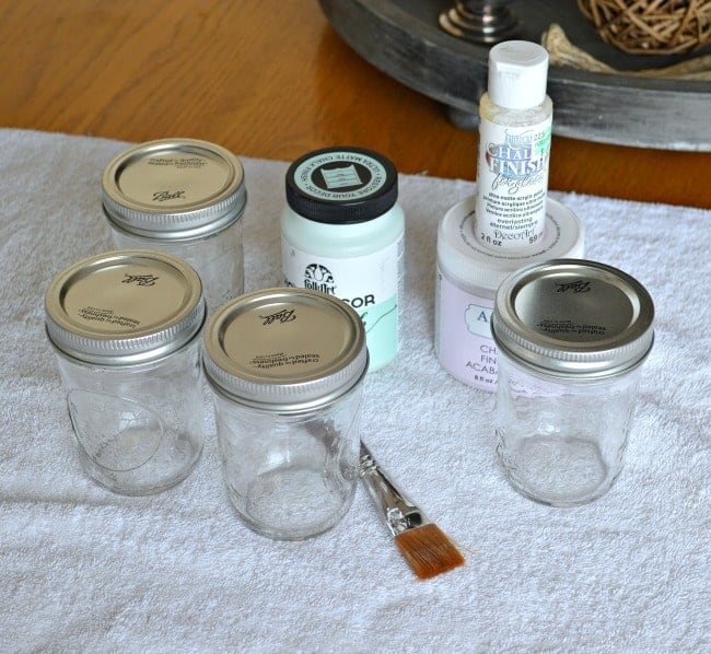 small mason jars with lids, a craft brush and 3 bottles of chalk paint