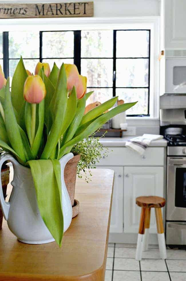 A pitcher of yellow and orange tulips on a butcher block island with kitchen window and wooden stool in the background