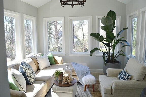 sunroom with sectional sofa and tall green plant