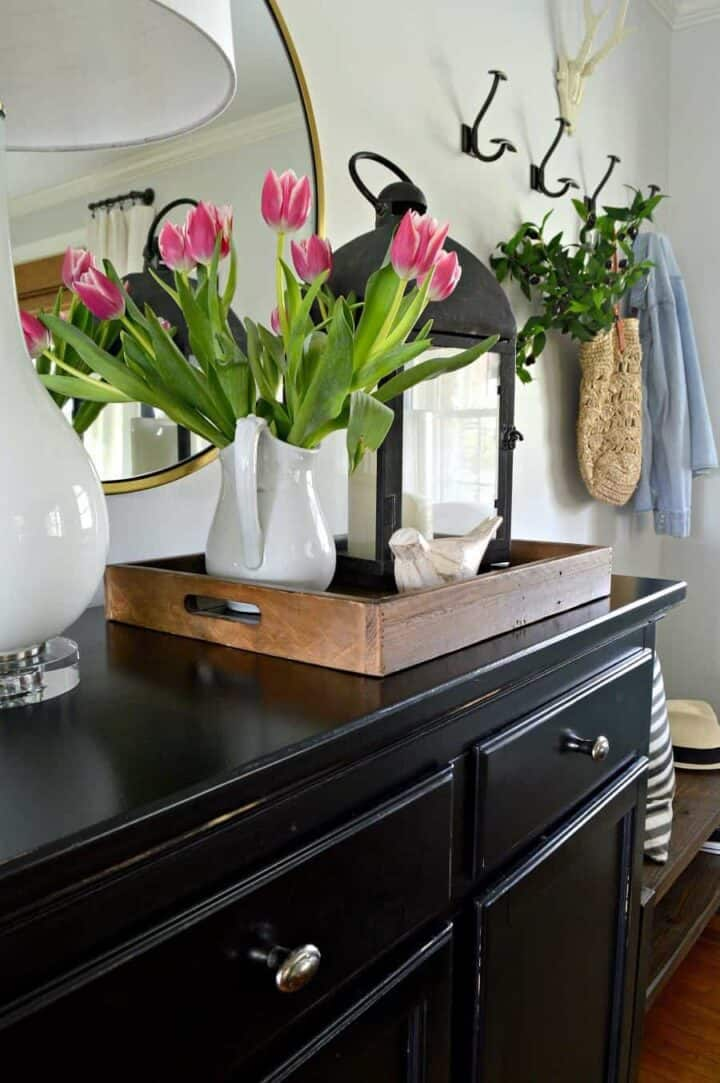 white pitcher filled with pink tulips on entryway console