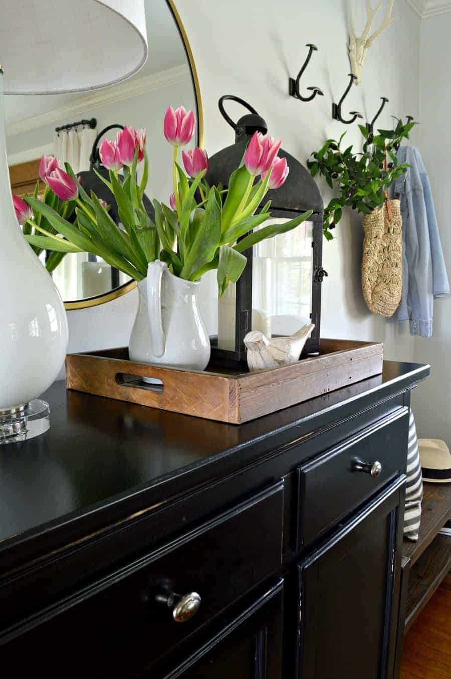 A vase of flowers on an entryway cabinet