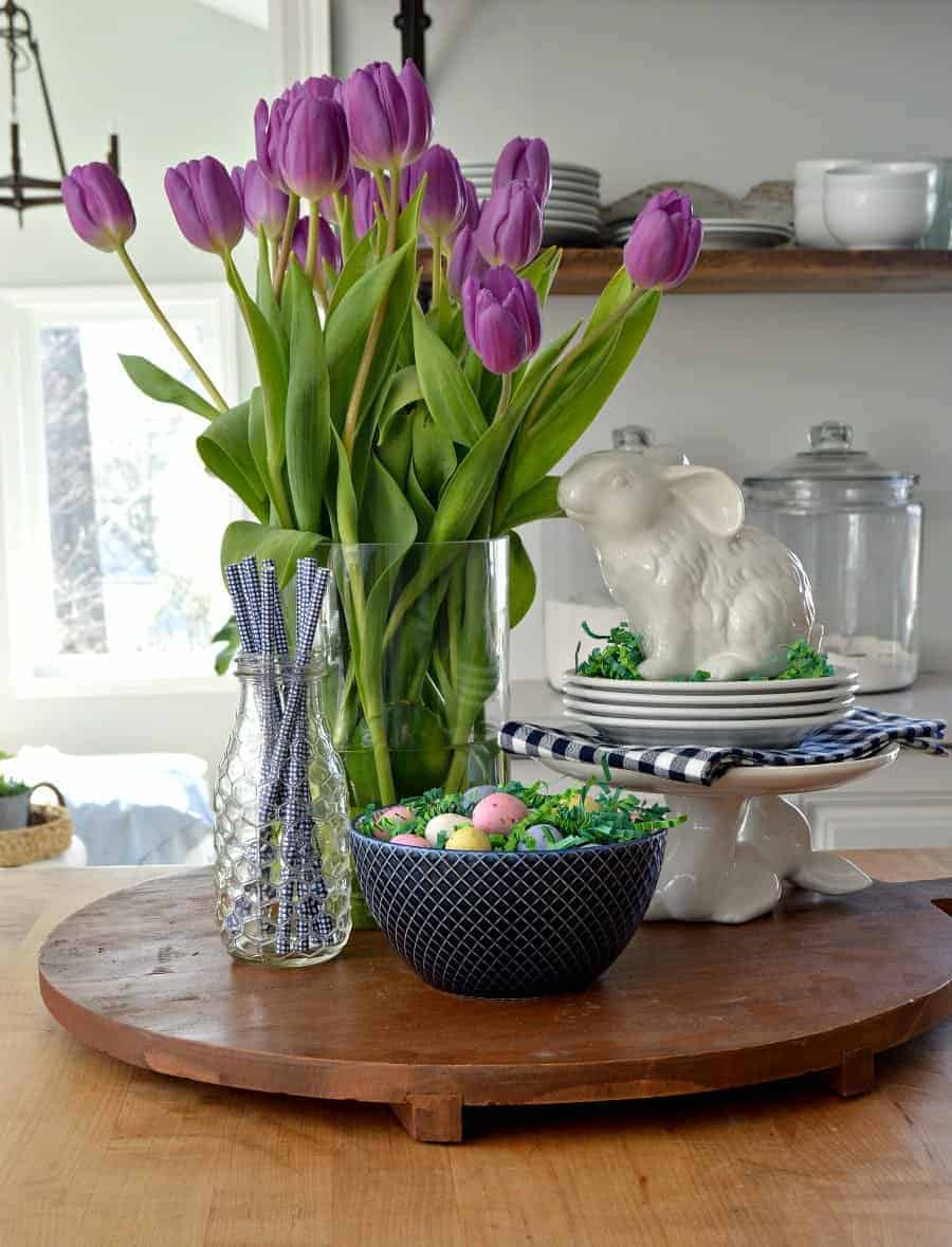spring vignette with purple tulips, white bunnies, blue straws in a glass bottle and a navy bowl with candy eggs