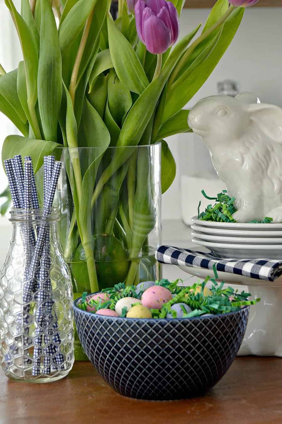 spring vignette with purple tulips, white bunnies, a blue checked napkin, blue straws in a glass bottle and a navy bowl with candy eggs