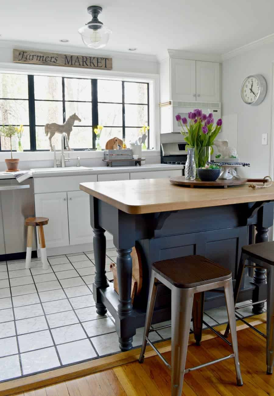 A kitchen with a spring vignette of purple tulips, white bunnies, and a navy bowl with candy eggs on a dark gray painted kitchen island