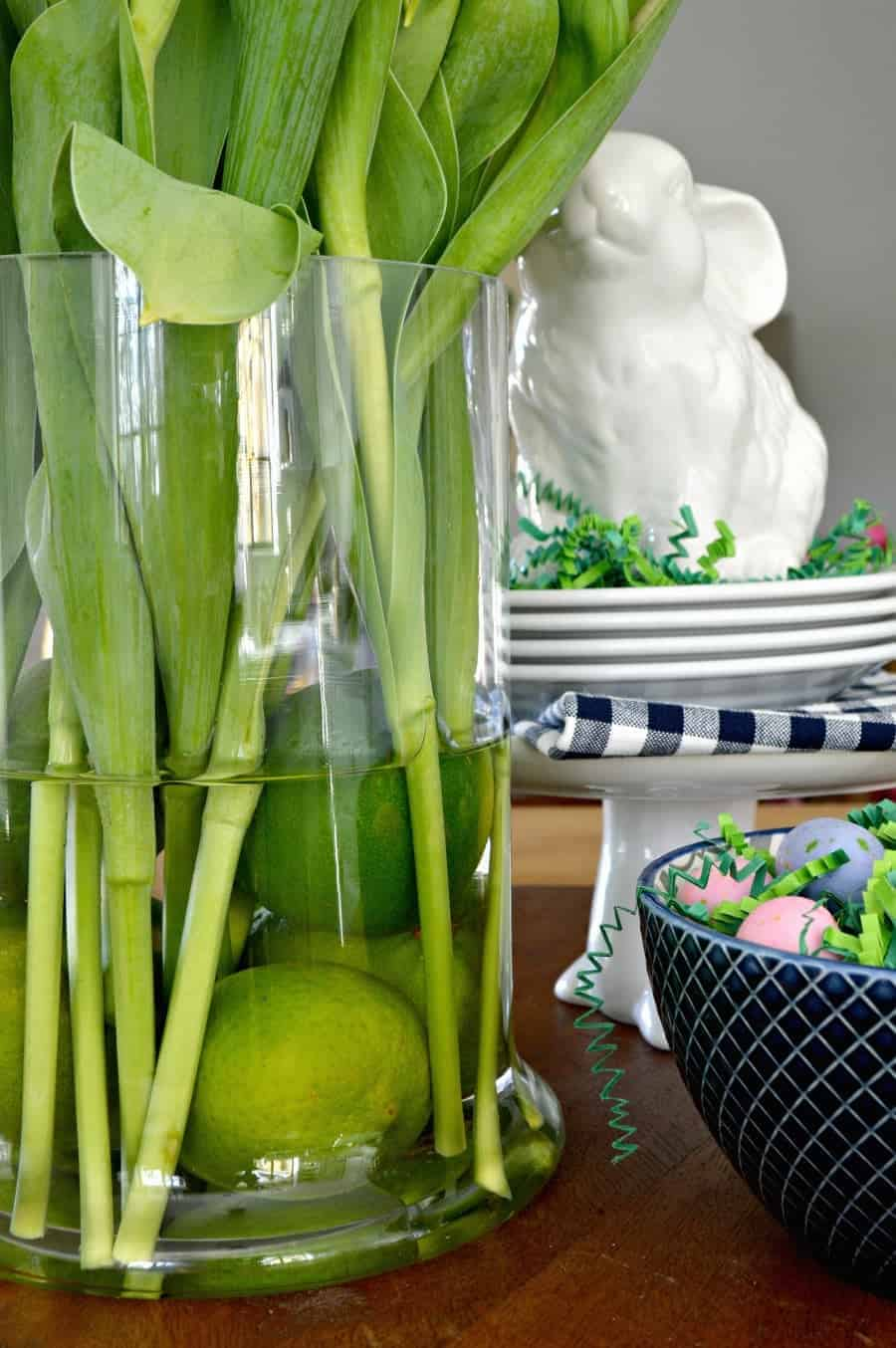 spring vignette with purple tulips in a glass vase with limes, a white bunny and a navy bowl with candy eggs
