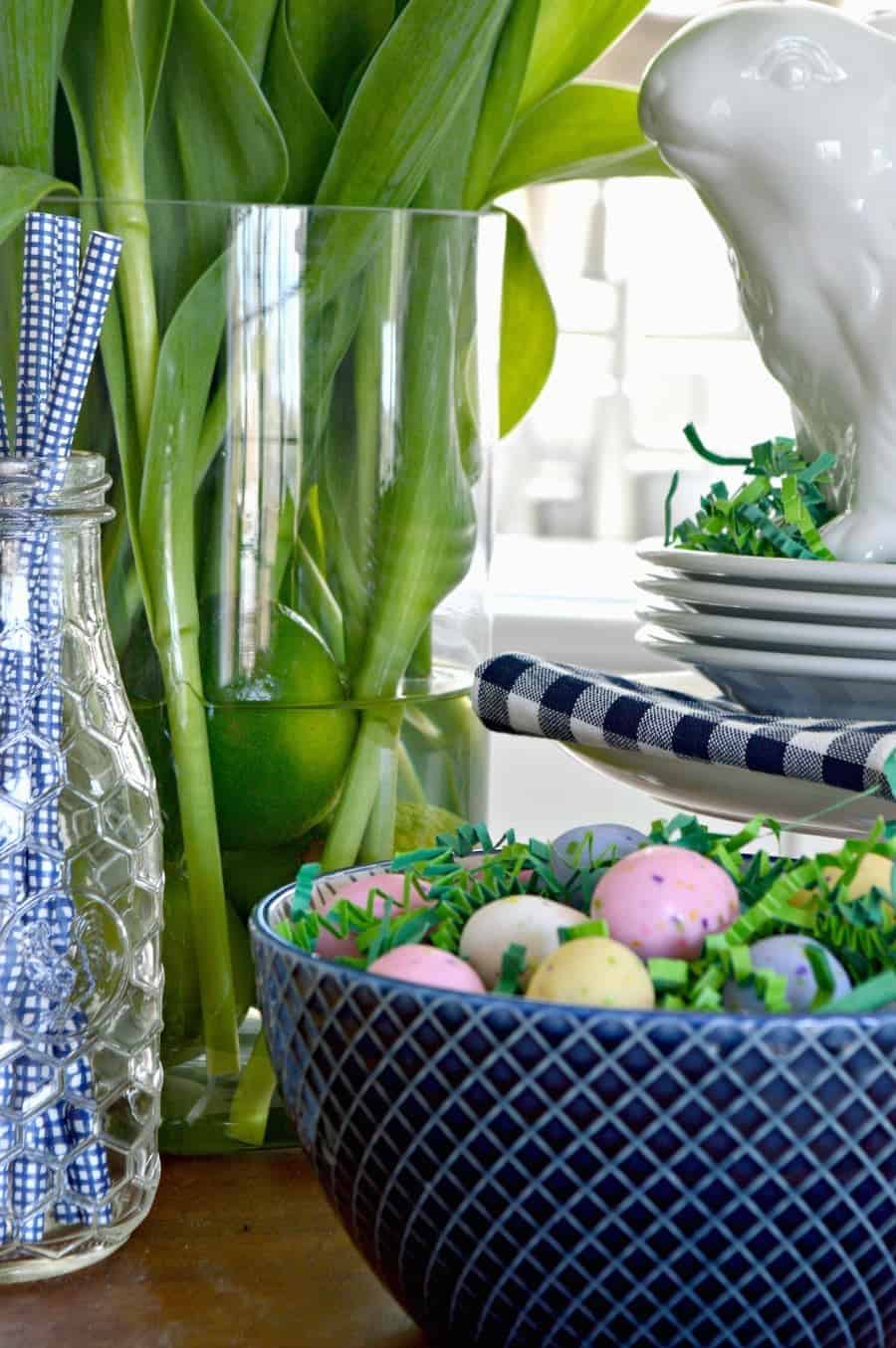 spring vignette with a white bunny, blue straws in a glass bottle and a navy bowl with candy eggs