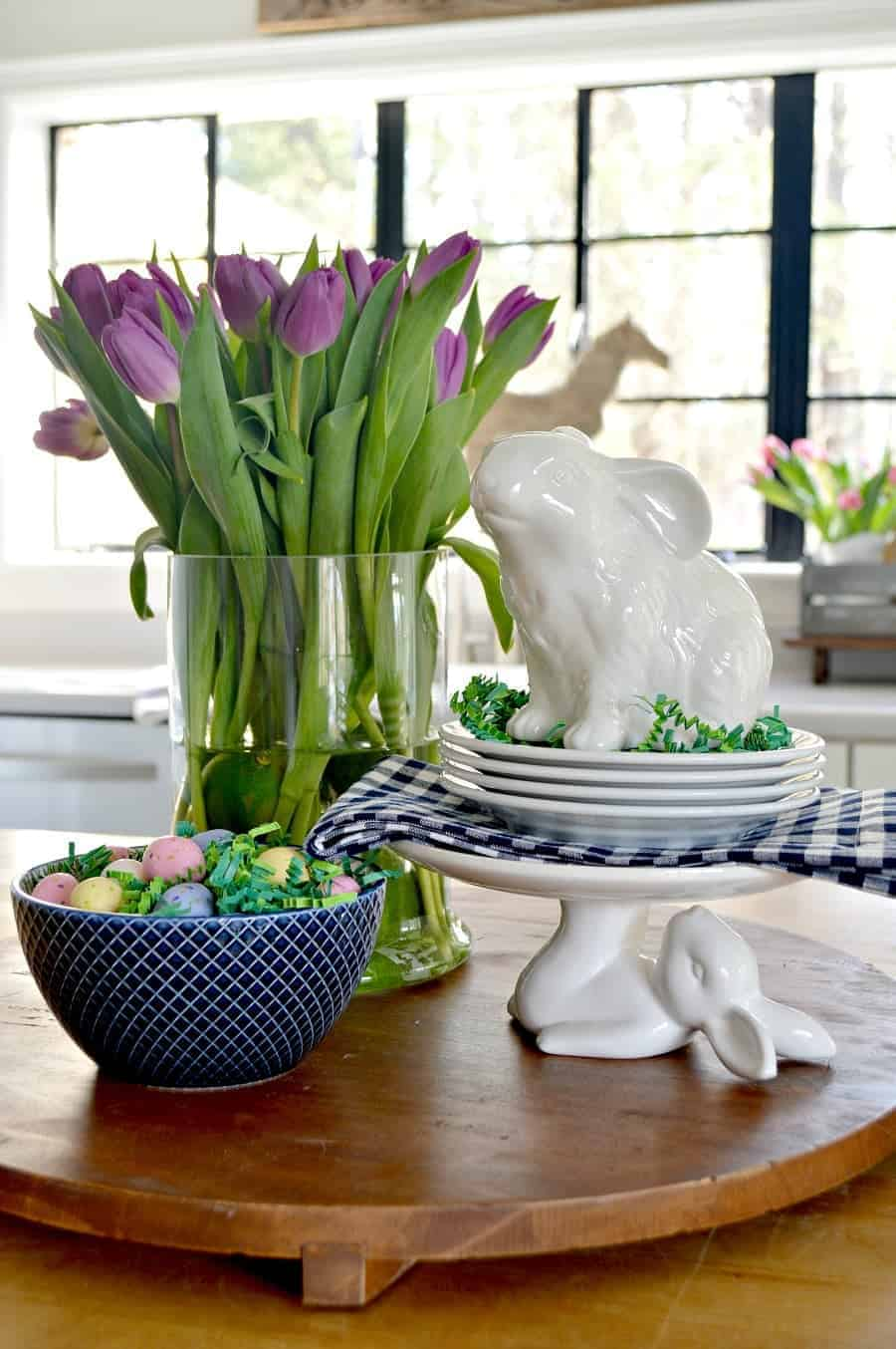spring vignette with purple tulips, white bunnies, a navy bowl with candy eggs on a large wood cutting board