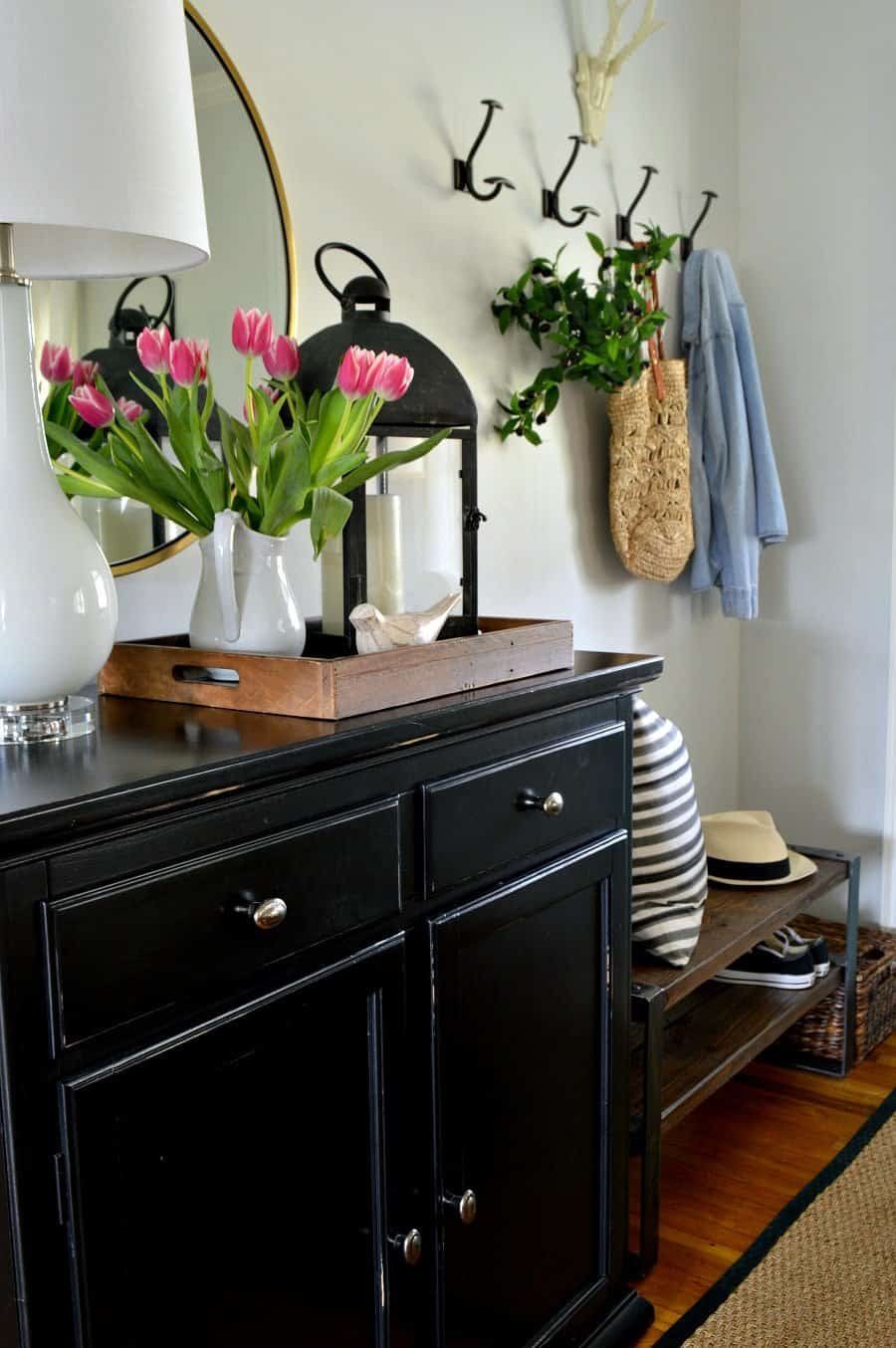 small entryway with pink tulips in pitcher on black cabinet