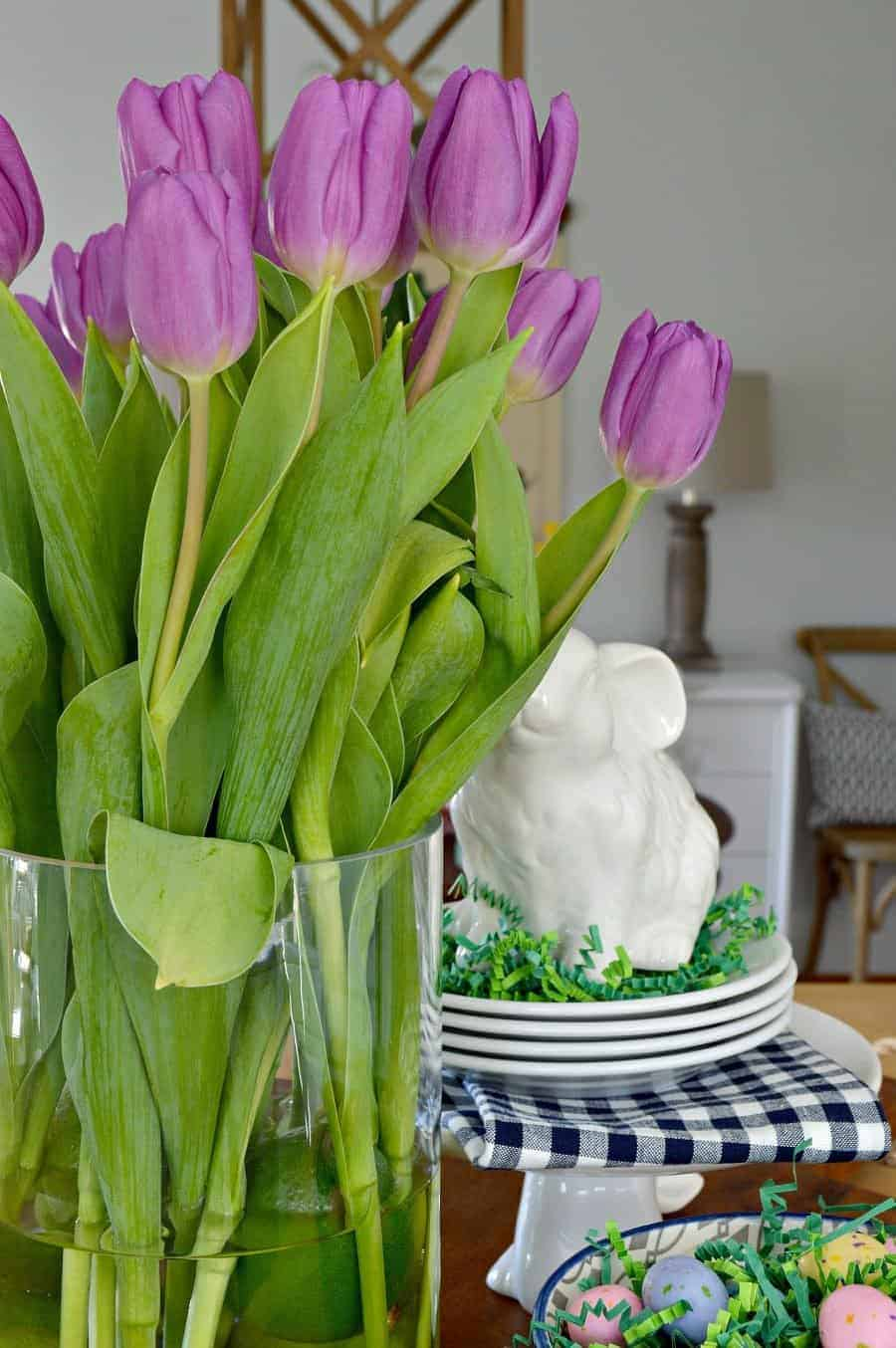 spring vignette with purple tulips, white bunnies, and a navy bowl with candy eggs