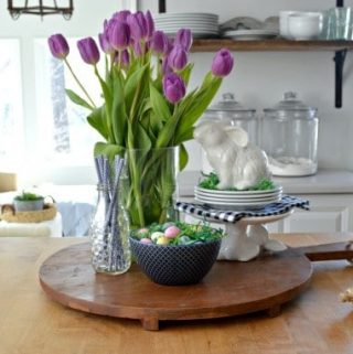 spring vignette with tulips in glass vase, candy eggs in blue ceramic bowl and ceramic bunny on top of bunny stand