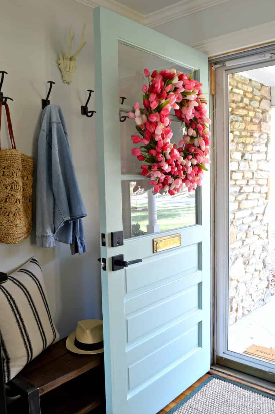 Pink tulip wreath hanging on blue painted farmhouse door.