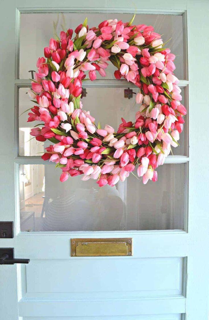 pink tulip wreath hanging on front door