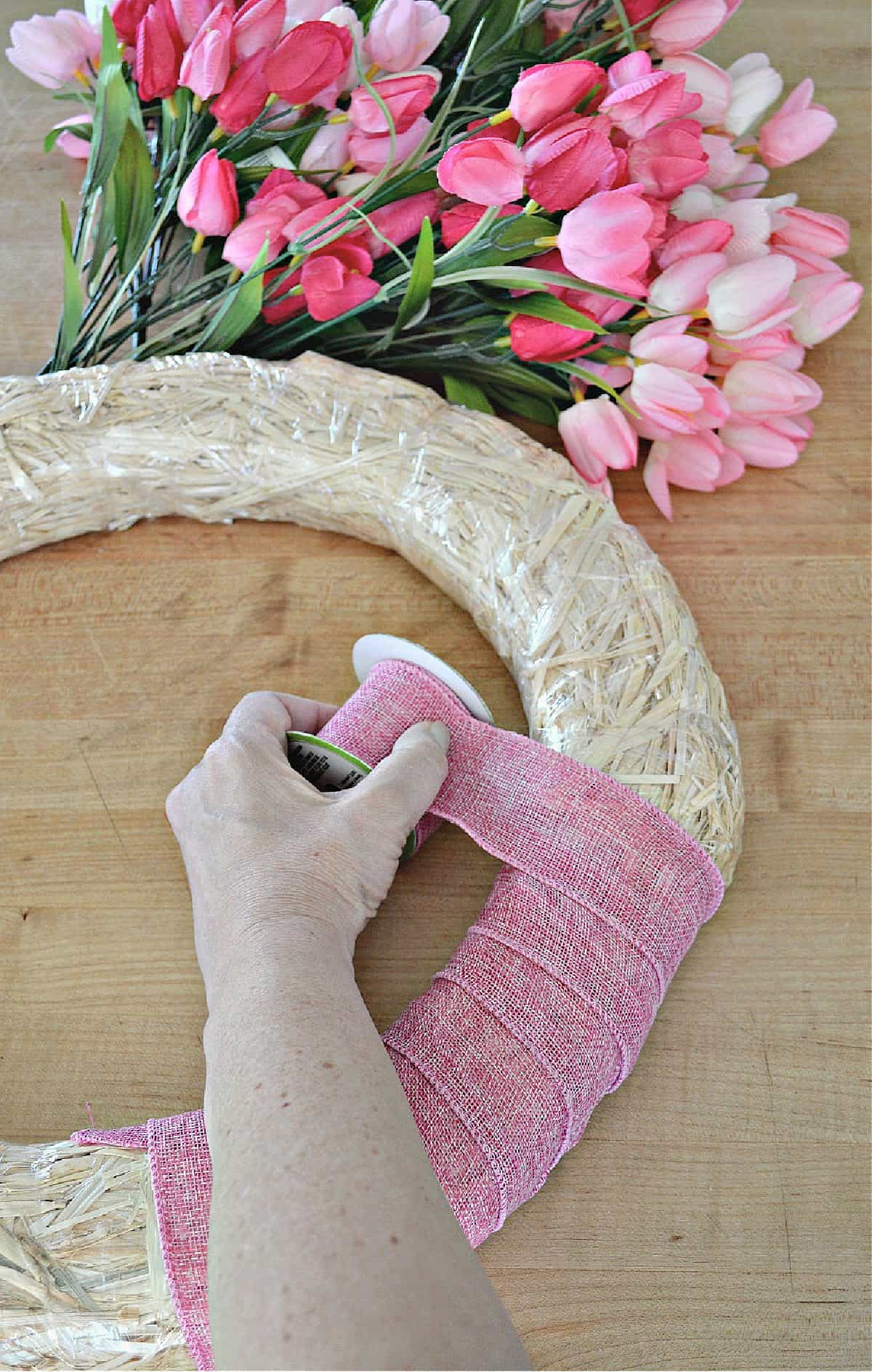 wrapping straw wreath form with pink ribbon