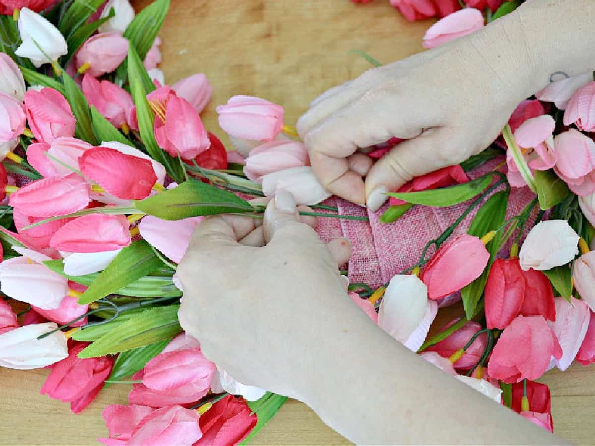 inserting pink tulip stem in ribbon wrapped wreath form