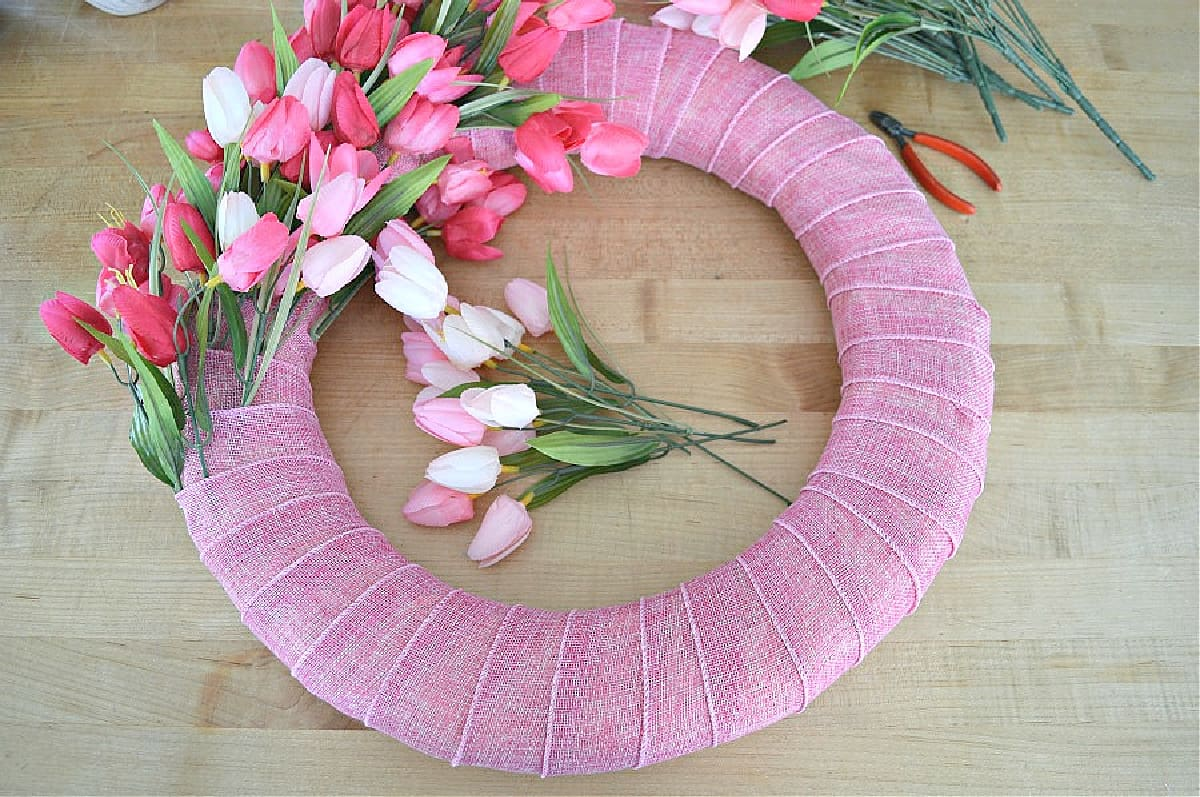 wreath form wrapped in pink ribbon with tulips added