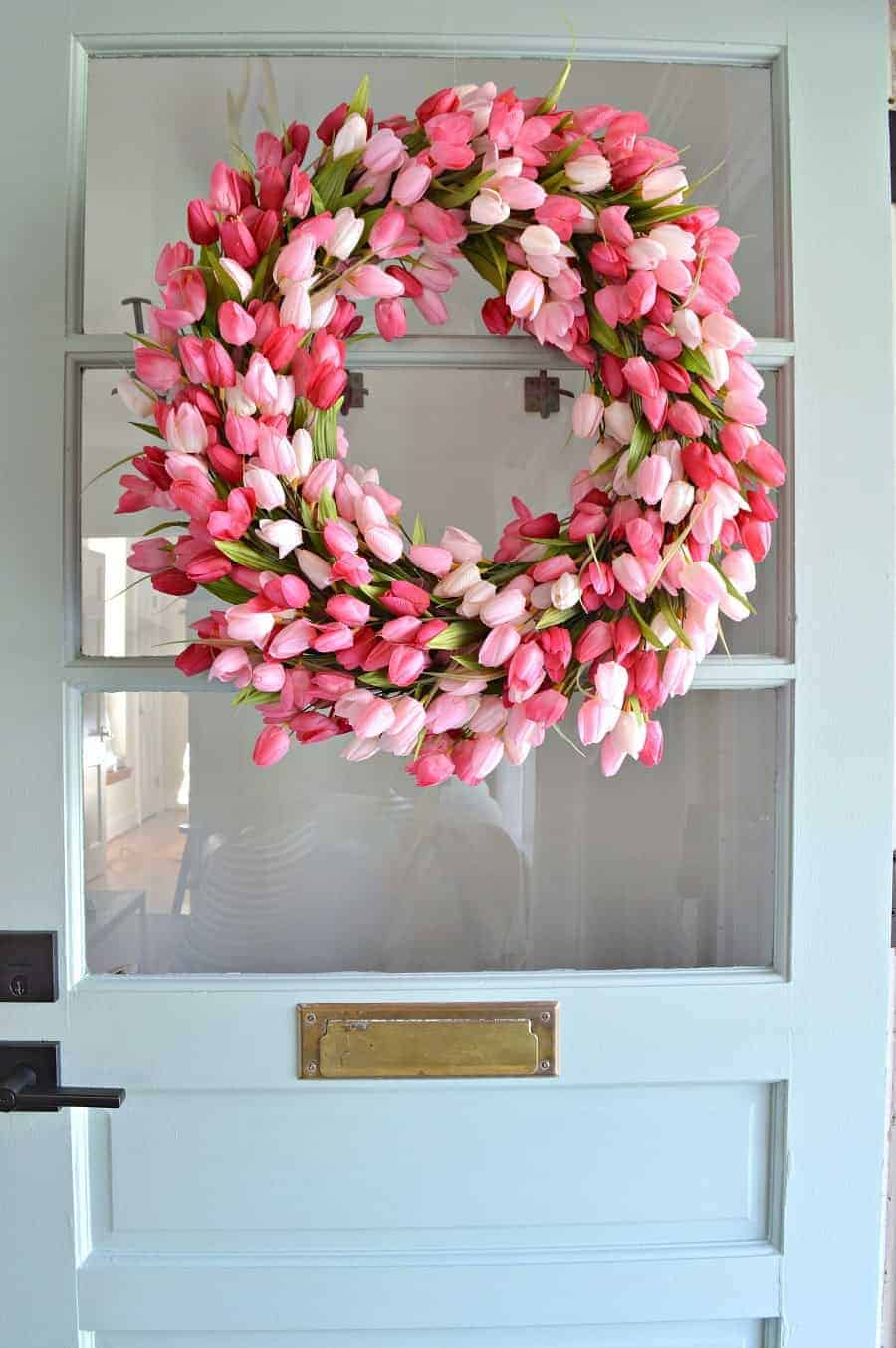 pink tulip wreath hanging on a blue farmhouse front door