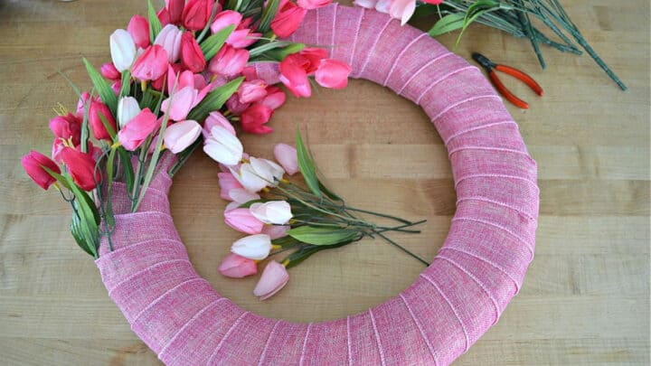 wreath form wrapped in pink ribbon and stuffed with pink tulips