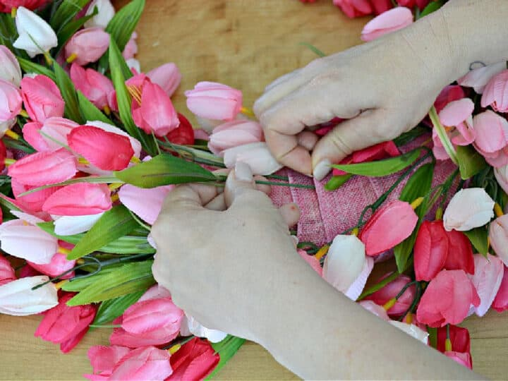 sticking pink tulips in ribbon on wreath