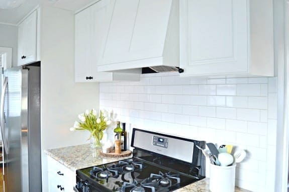 stove side of galley kitchen with white paintedcabinets