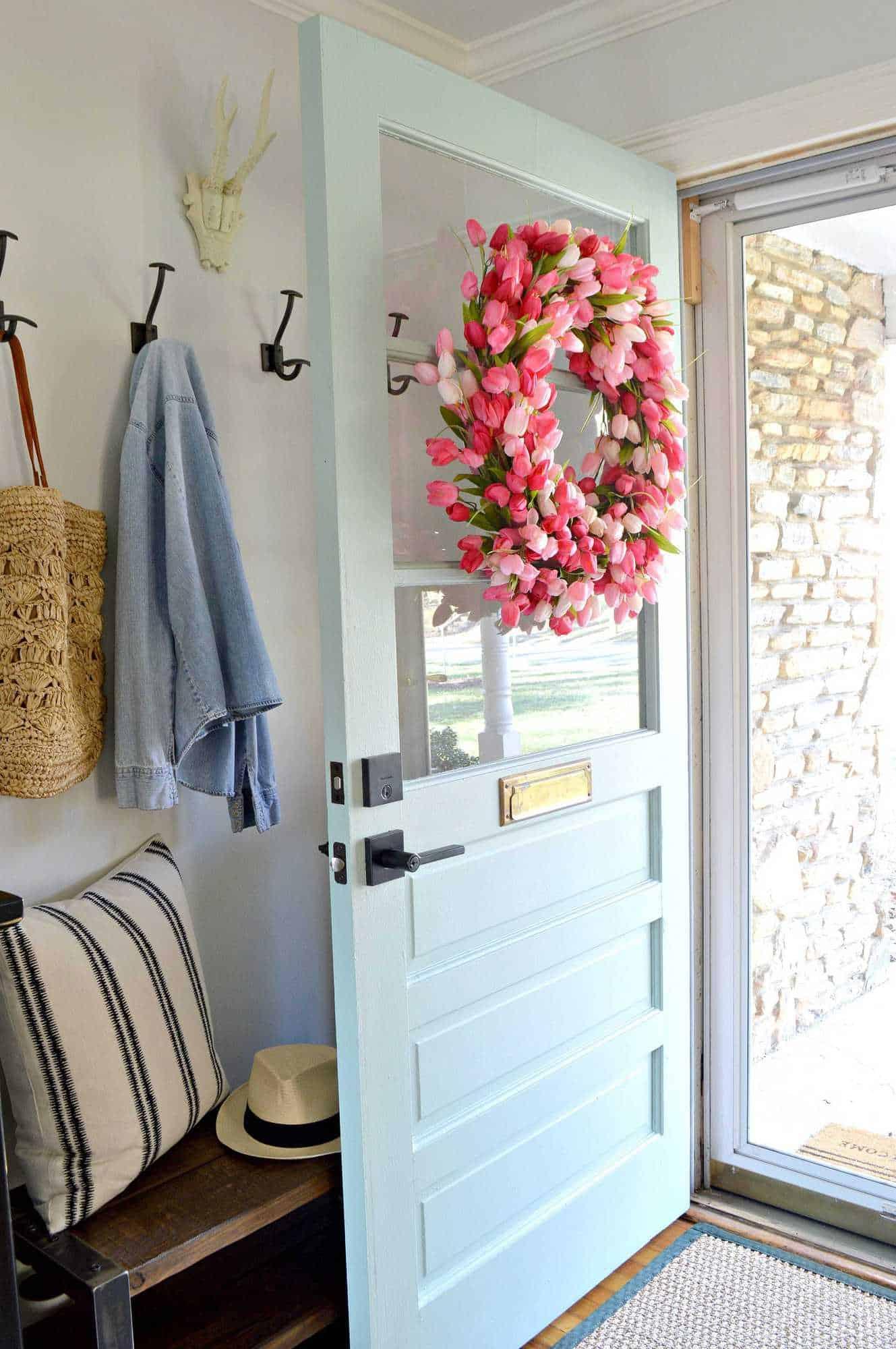 DIY pink tulip wreath on light blue farmhouse front door
