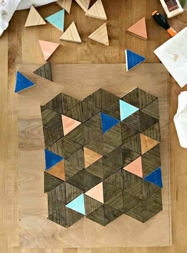 stained and painted wood triangles arranged in a square shape