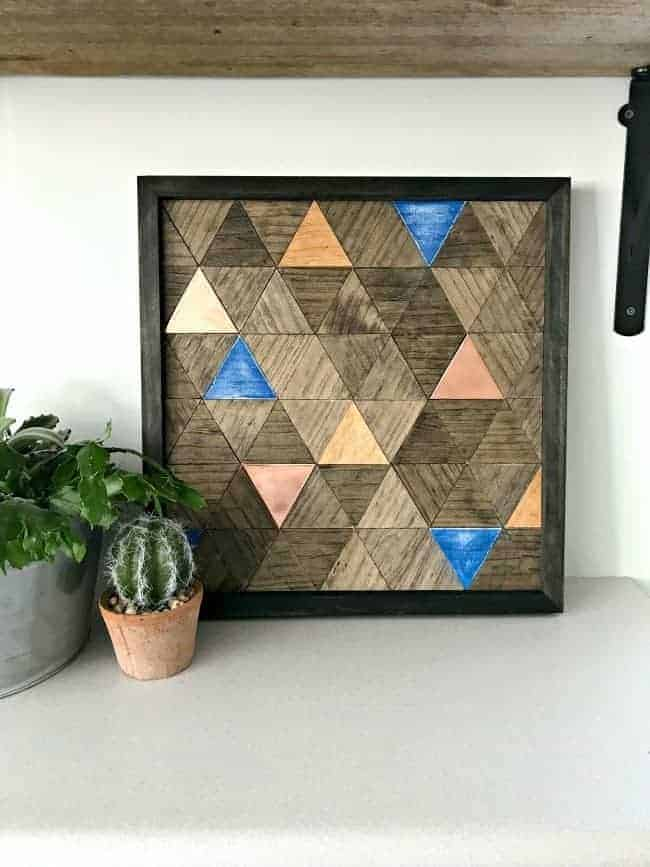 wood wall art with potted succulents