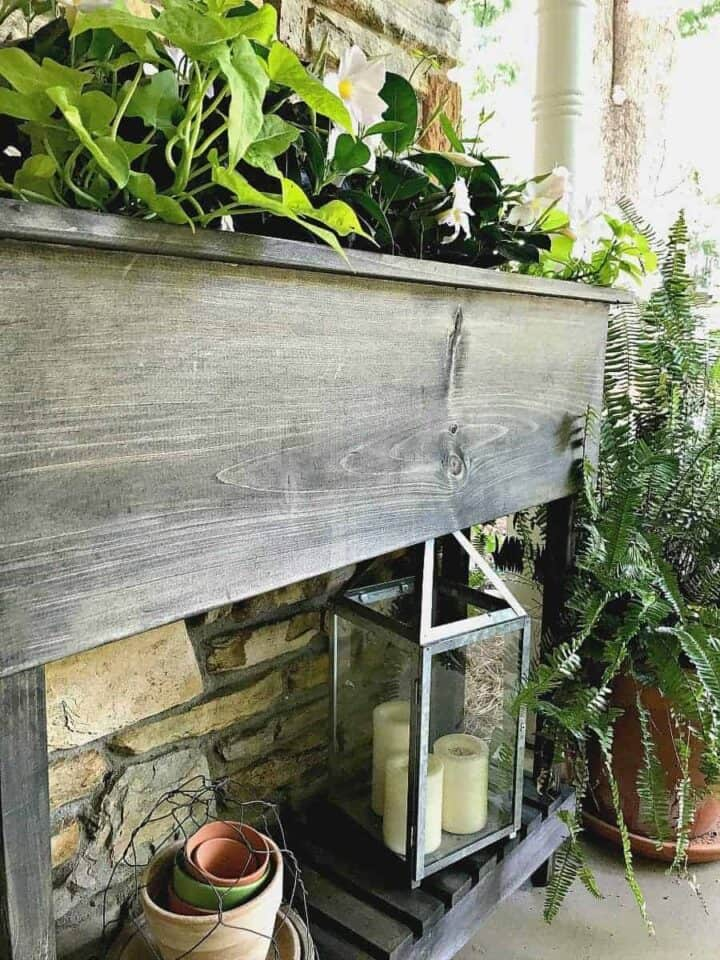 DIY wood raised planter with legs on front porch with white flowers planted in it.