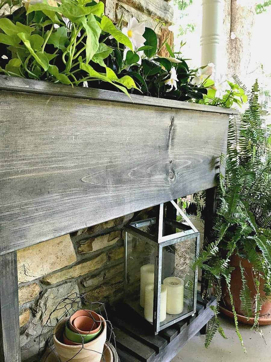 DIY wood planter on front porch with white flowers planted in it.