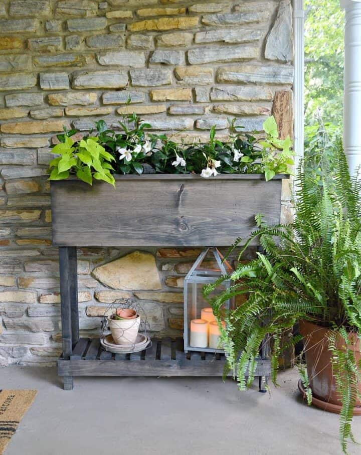 DIY raised planter box with legs on front porch of stone cottage