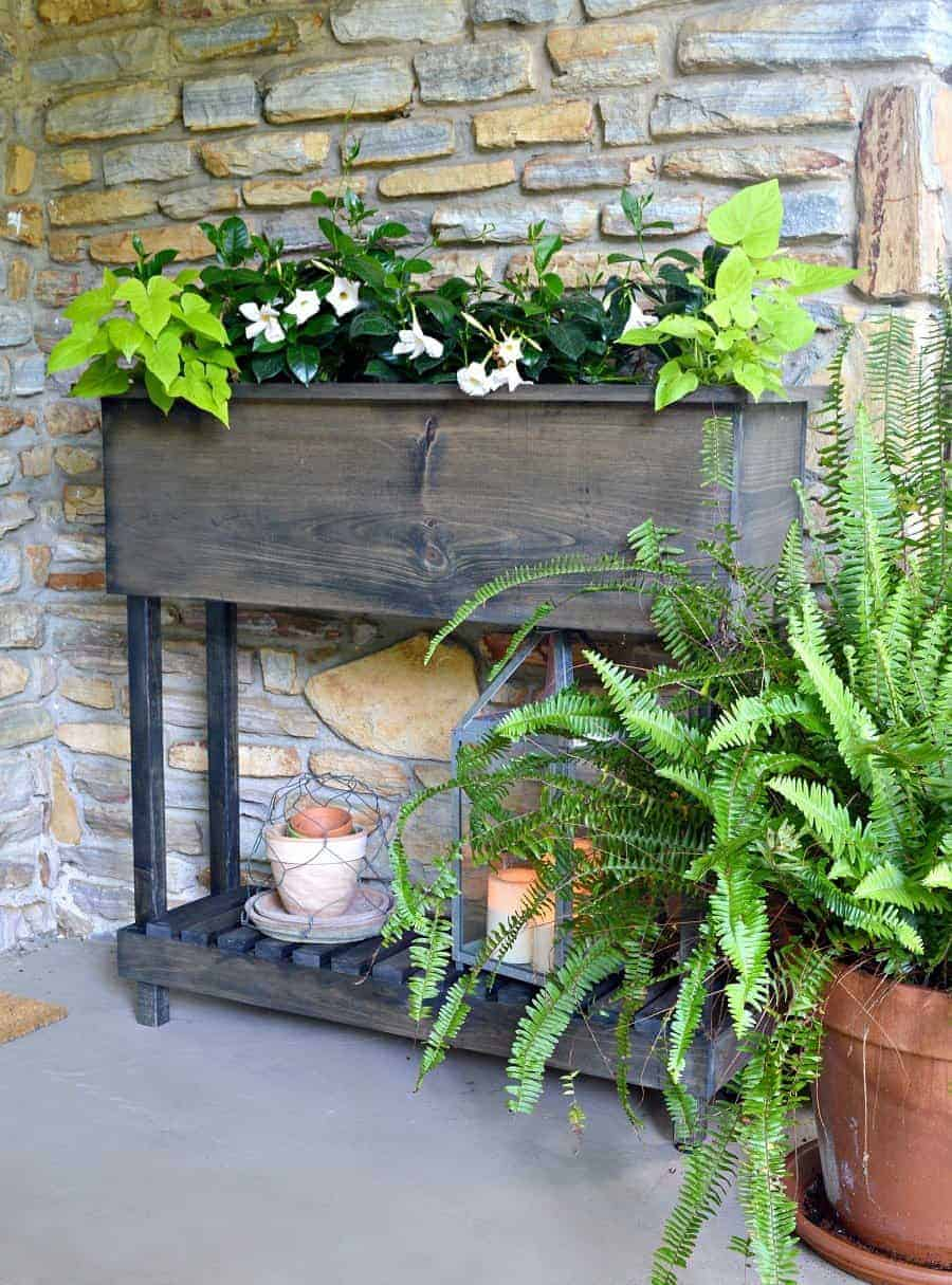 finished DIY wood planter box with flowers planted in it and old pots on bottom shelf