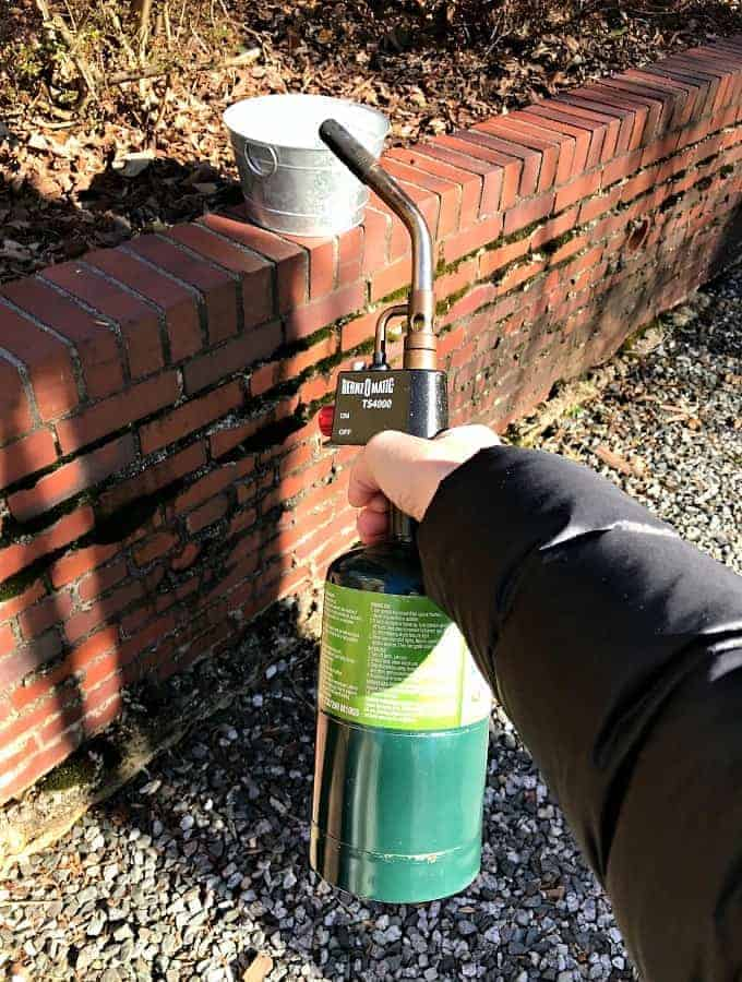 propane torch used to age galvanized bucket for a DIY succulent planter