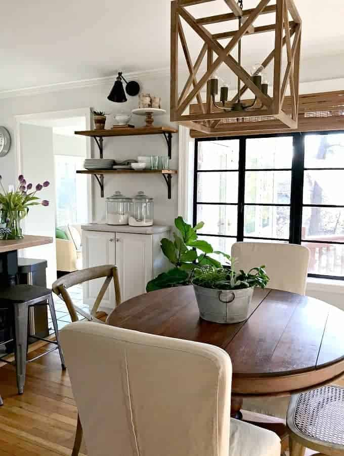 round kitchen table with wood hanging fixture above it and barn wood shelves in the background