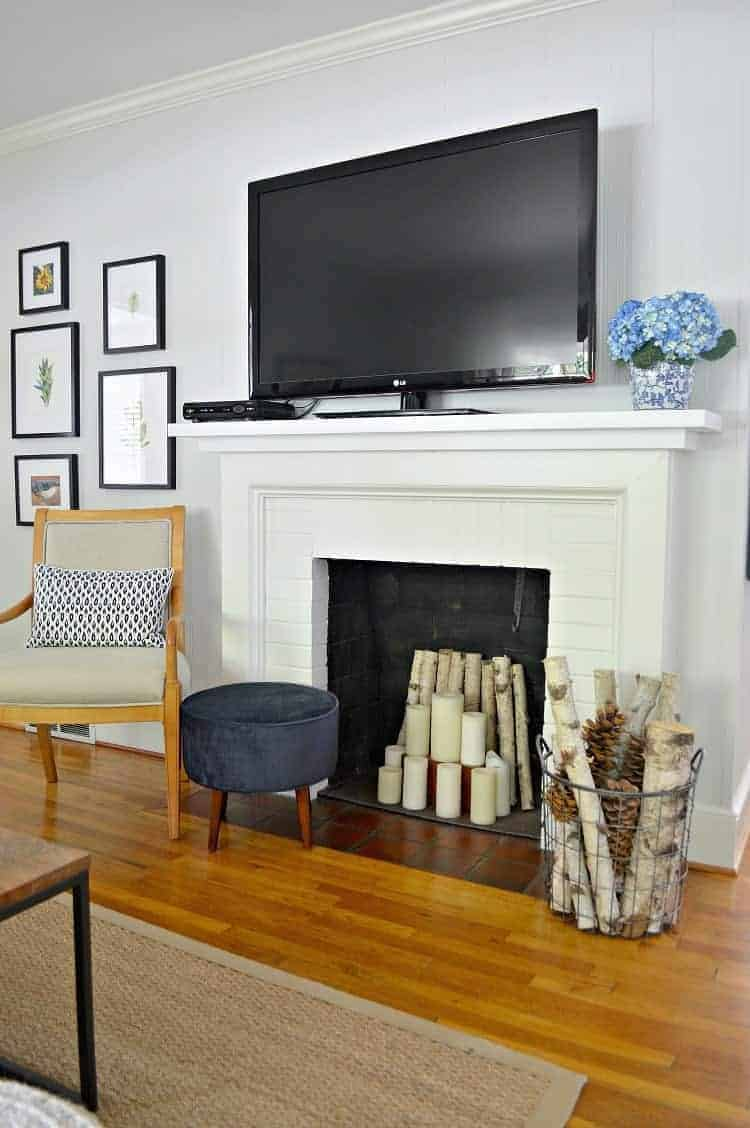 flat screen tv on white fireplace mantel with chair next to it