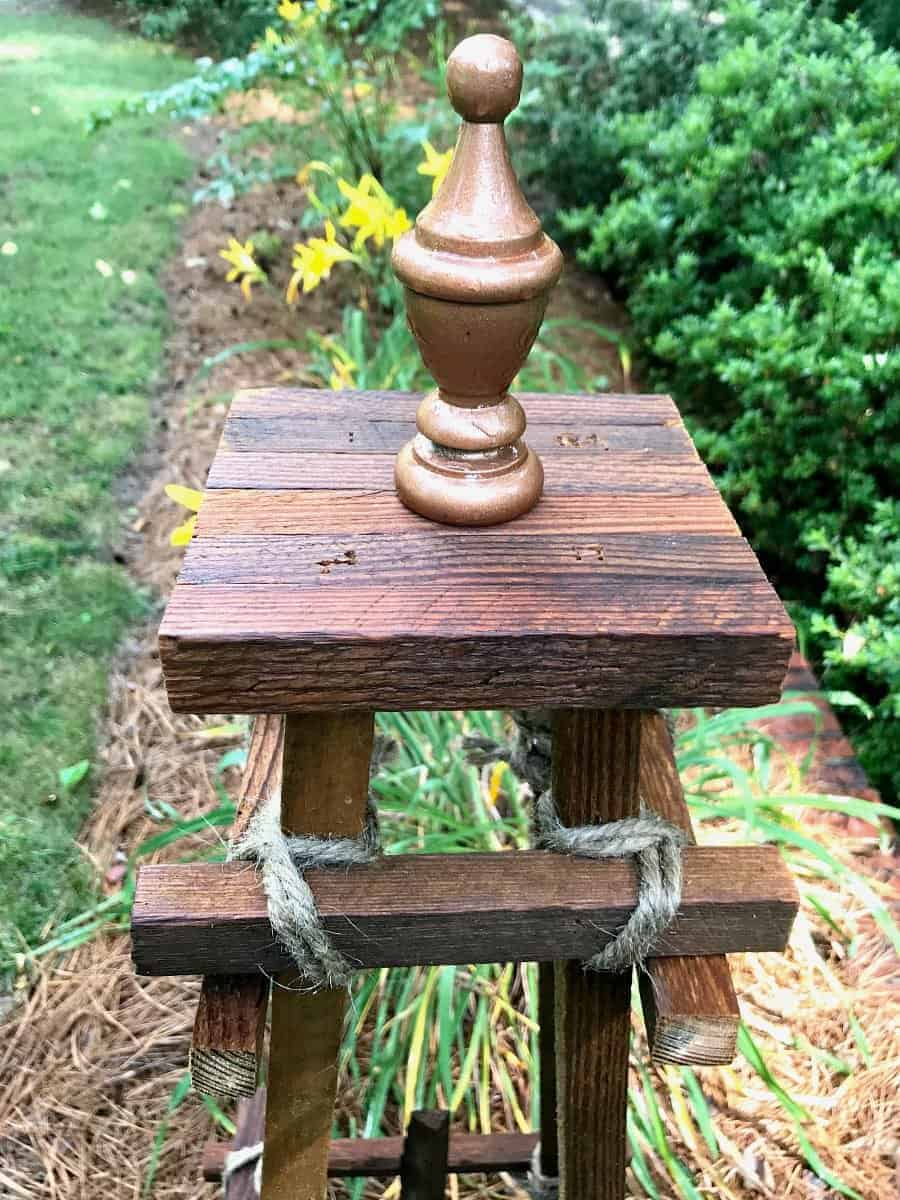 top half of a wooden garden obelisk sitting in the middle of a garden with daylilies