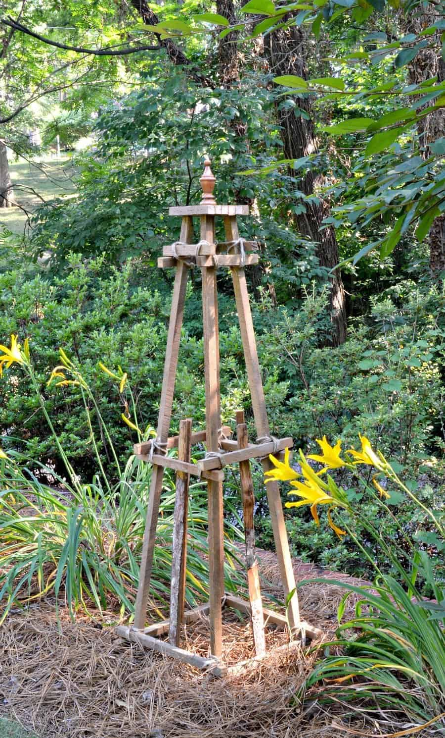 wooden garden obelisk sitting in the middle of a wooded garden with daylilies