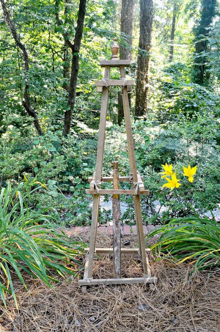 a DIY wooden garden obelisk sitting among the daylilies in a garden