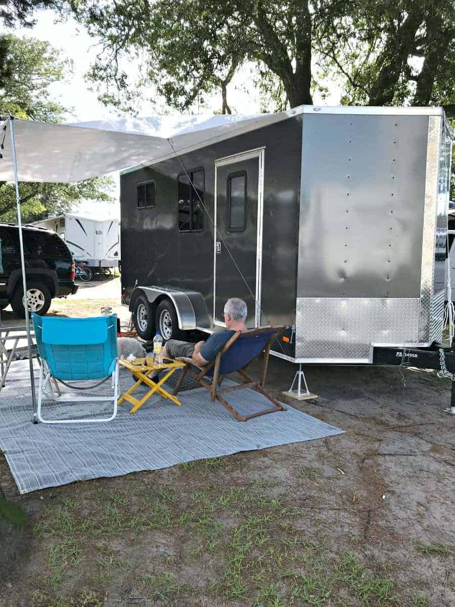 little RV set up for camping with chairs and white awning