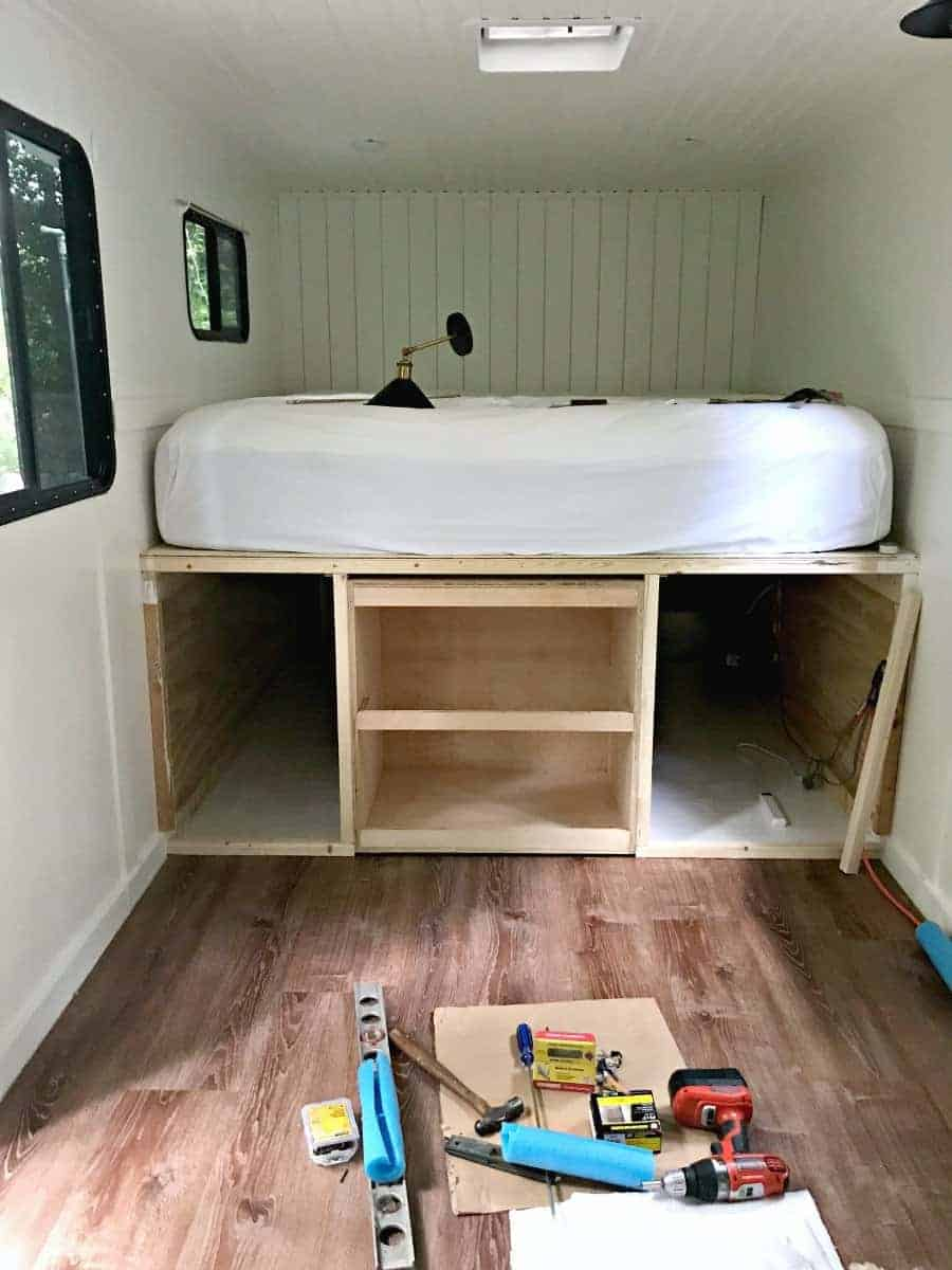 tiny RV with view of platform bed and underneath storage