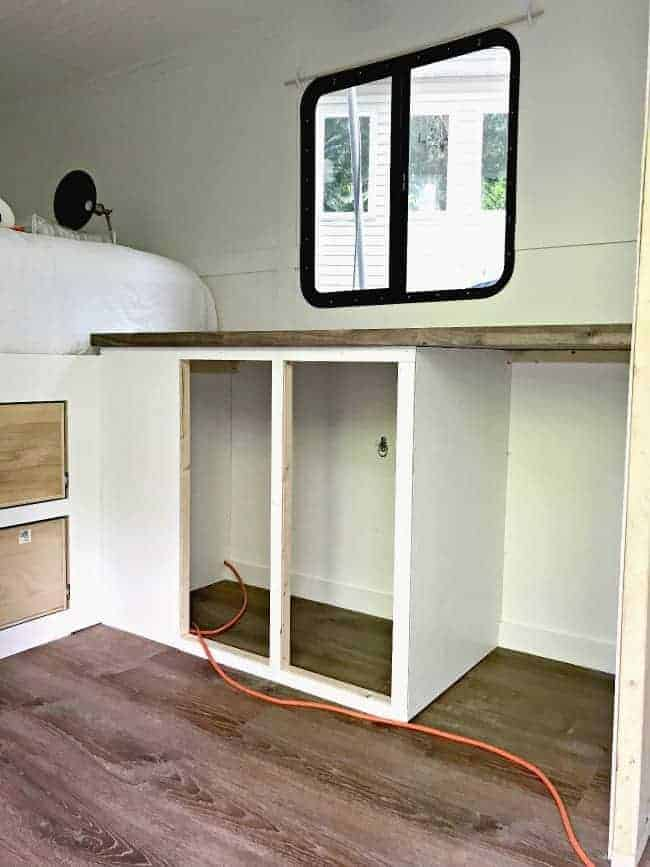 newly built kitchen cabinets and butcher block countertop installed in cargo trailer conversion