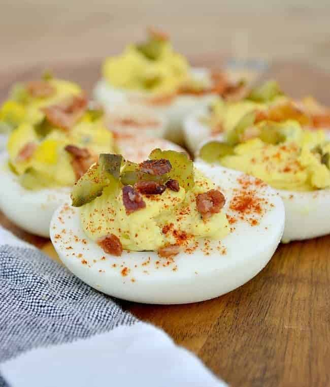 deviled eggs on a wooden board with bacon, pickles and paprika sprinkled on top