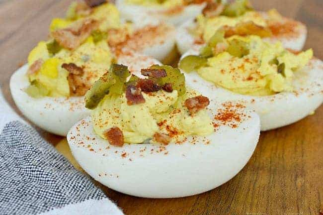 deviled egg halves with pickles and bacon on top on wood board with black and white towel in corner