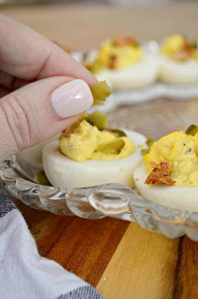 garnishing deviled egg half with diced pickle
