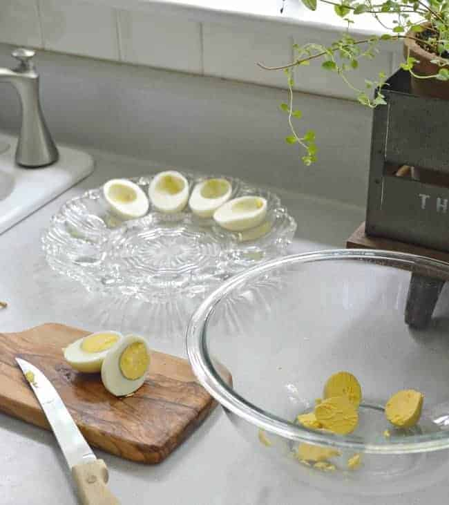 cutting hardboiled eggs in half and yolks in clear glass mixing bowl