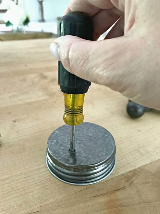 making DIY mason jar lanterns, using an awl to poke holes in mason jar lid