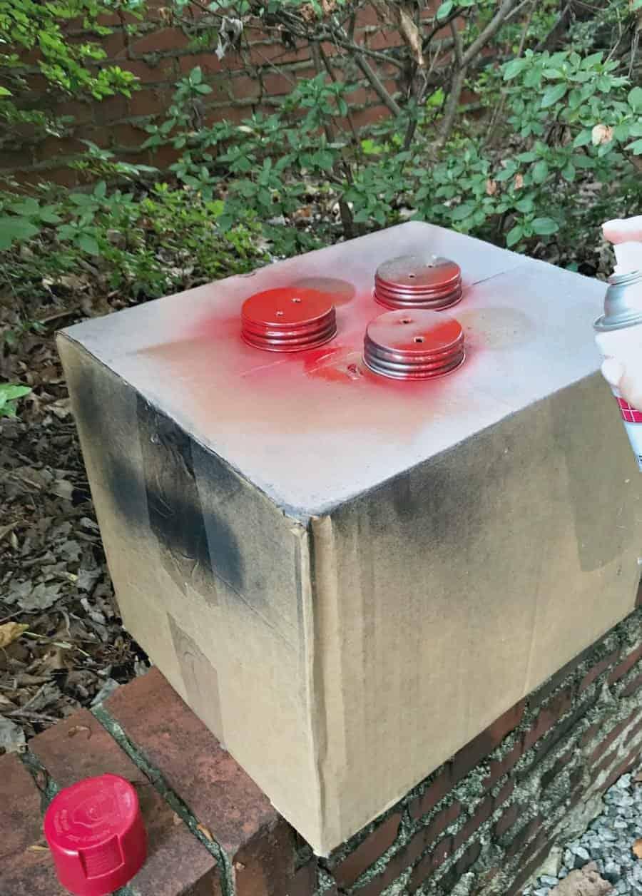 making DIY mason jar lanterns, spray painting mason jar lids red