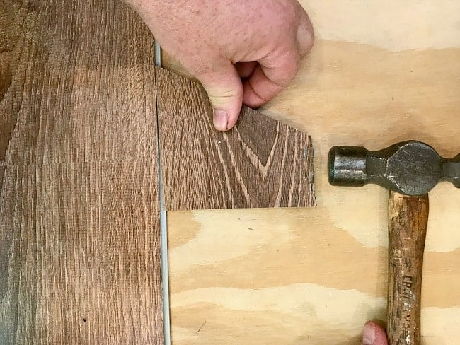 tapping scrap piece of vinyl plank flooring with a hammer