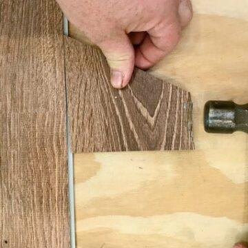 hammering a piece of vinyl plank floor during installation
