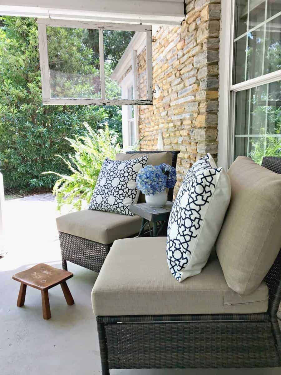 two wicker chairs on porch with blue and white pillows and a little footstool