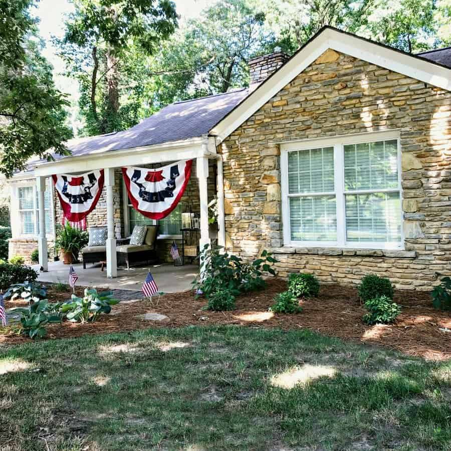 stone cottage with red, white and blue buntings hanging on covered front porch