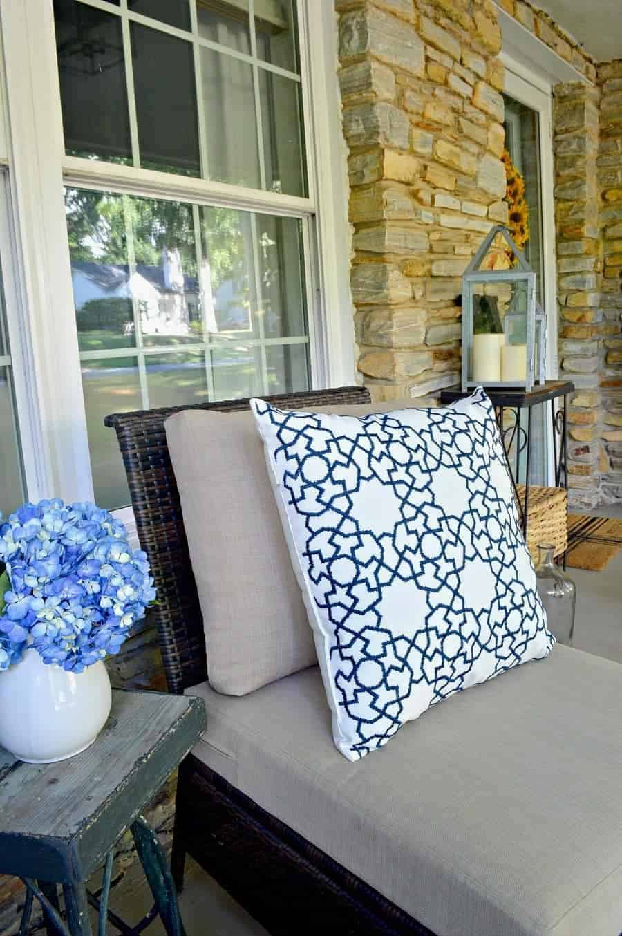 wicker chair on porch with blue and white pillows and blue hydrangeas in a white pitcher
